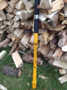 Splitting firewood logs, using a hand-held logsplitter