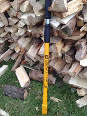 Splitting firewood logs, using a hand-held logsplitter