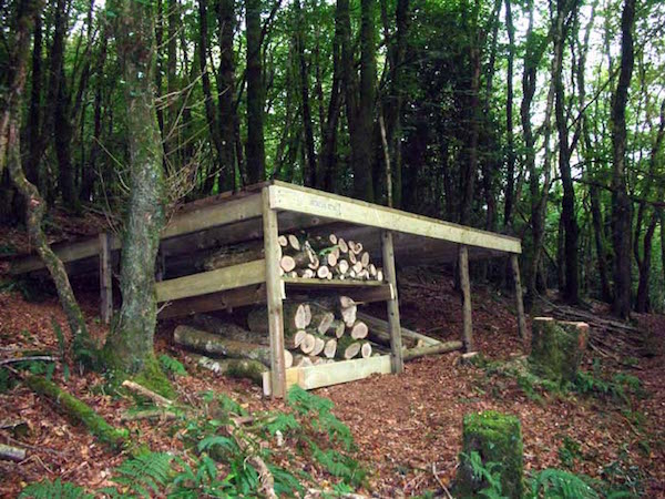 """use the space under a platform on a slope for a log store"""