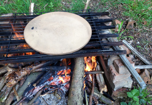 Cooking pizza on a campfire in a woodland